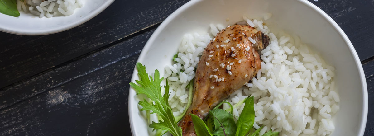 chicken drumstick with herbs on top of white rice