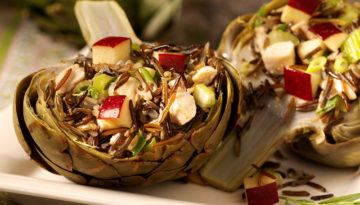 Side view of artichokes stuffed withchicken and wild rice on a white plate.