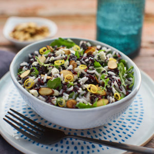 Side view of arugula and rice salad in a blue bowl.