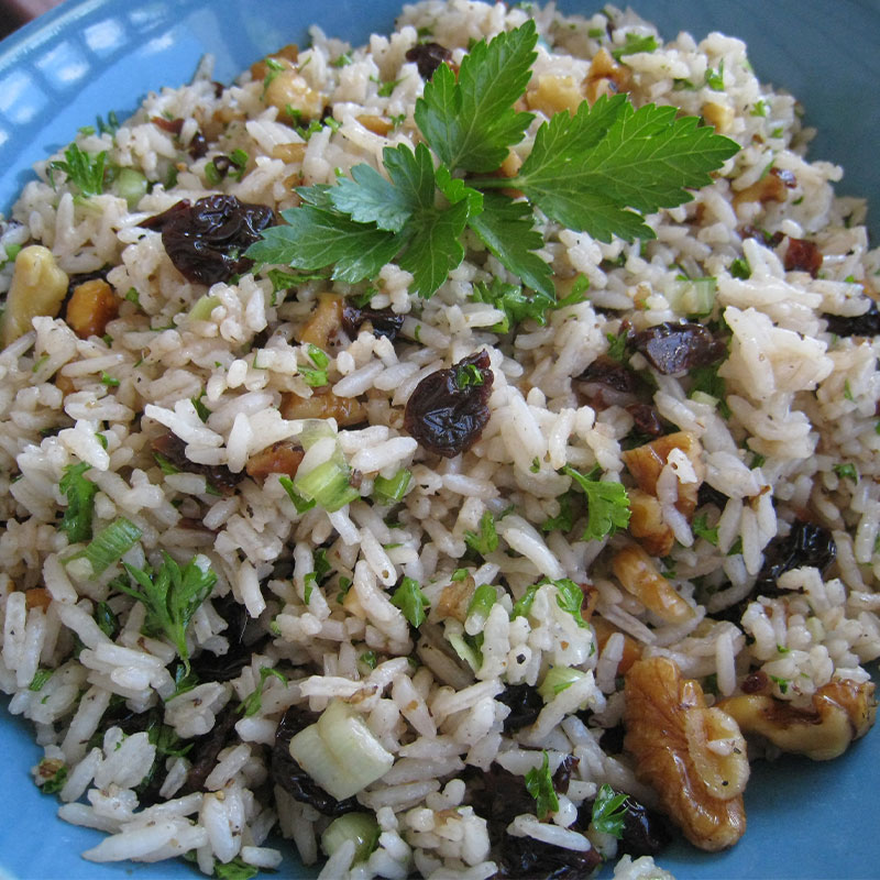 Overhead image of Balsamic Cherry Rice Salad with Toasted Walnuts in a blue bowl