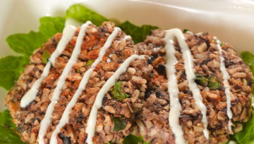 Overhead shot ofBlack Bean & Brown Rice Cakeson a bed of lettuce