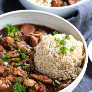 Side view of chicken and sausagegumbowithbrown rice in a white bowl