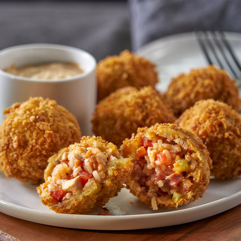 Side shot of a plate full of 6 Jambalaya Arancini balls with dipping sauce to the side