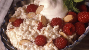 Raspberry Rice Pudding topped with Raspberries, sliced almonds, whipped cream, and basil in a bowl.