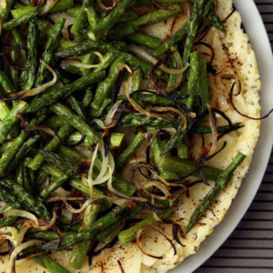 Overhead shot of a completeSwiss & Asparagus Rice Tarttopped with asparagus halves and onion.
