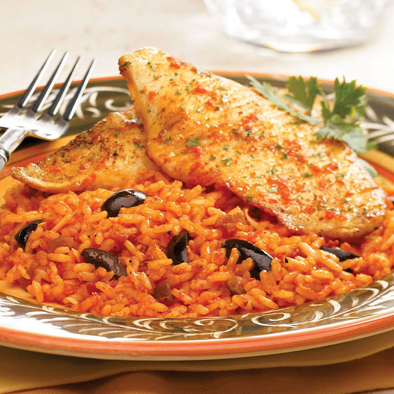Two pieces of seasoned tilapia on top of cheesy rice