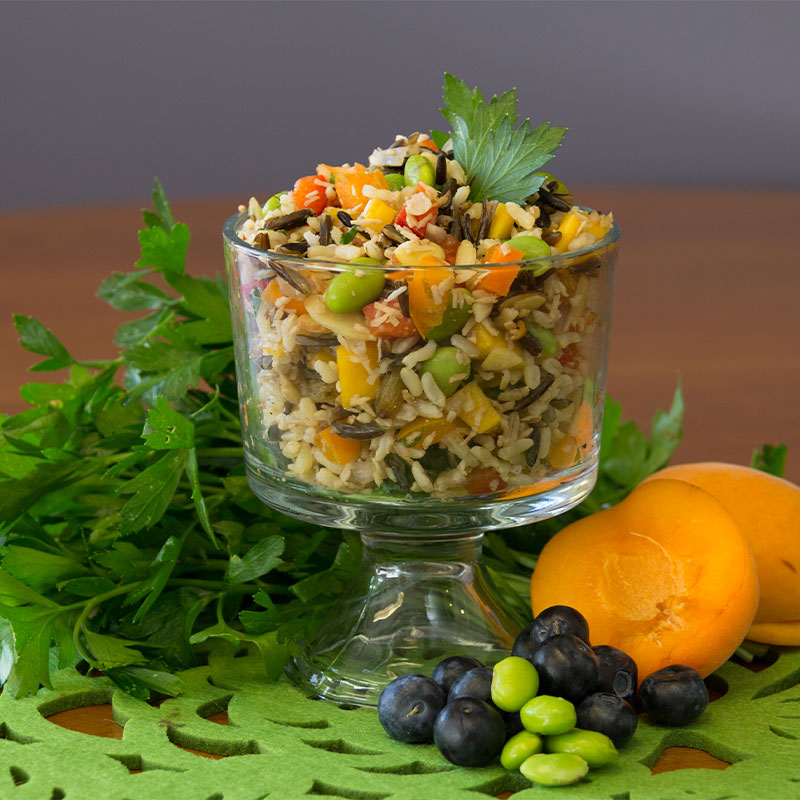 A transparent cup filled with tropical wild rice medley salad